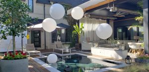 Classic white flaoting balloons over a pool